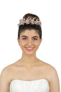 Pale Rose Gold Tiara of flowers and leaves worn by a smiling dark hair bride in front of a white backdrop