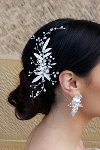 Dark hair Bride wearing a silver and leaf comb at the back of her head with a matching earring.