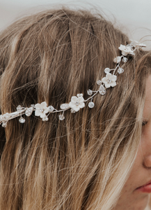 A model with tousled blonde hair wears a flower vine in a bridal hairstyle