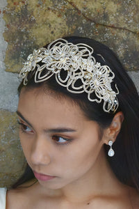 Matt Gold Headband worn at the front of the head on a black hair model with a stone wall behind