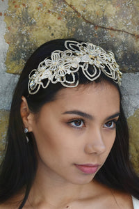 Matt Gold Bridal Headpiece worn by a dark hair model with a stone wall behind her.