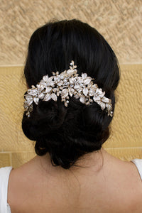 A Thick Pale Gold Short Bridal Vine on a dark hair model at the back of the head with a sandstone backdrop