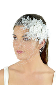 A white lace side comb with a fascinator veil attached worn by a dark haired model