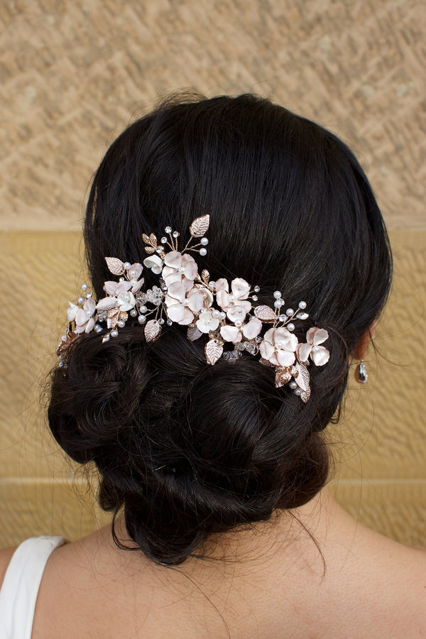 Bride wears a Pale Rose Gold Bridal headpiece in her dark curly hair with a stone wall background
