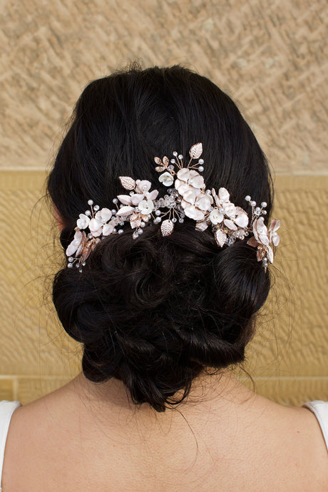 Bride with curling black hair wears a pale rose gold flowers headpiece on the back of her head. A stone wall is the background