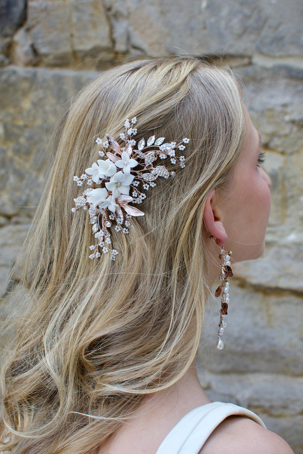 Pale Rose Gold bridal side clip with Porcelain flowers and pearls worn by a blonde model on the side of her head