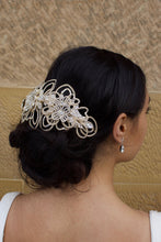 Load image into Gallery viewer, At the rear of her head a bride wears a Matt Gold Hair Comb with a stone wall behind her