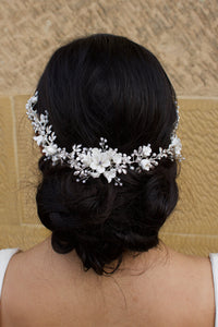 A black haired Bride wears a porcelain flowers silver vine around the back of her head with a stone wall behind