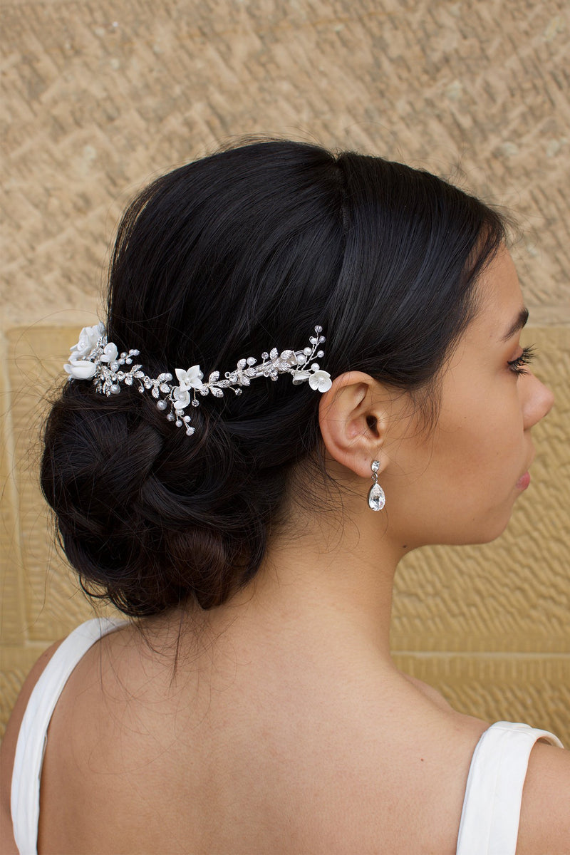 Side view of a black haired Bride wears a porcelain flowers silver vine around the back of her head with a stone wall backdrop