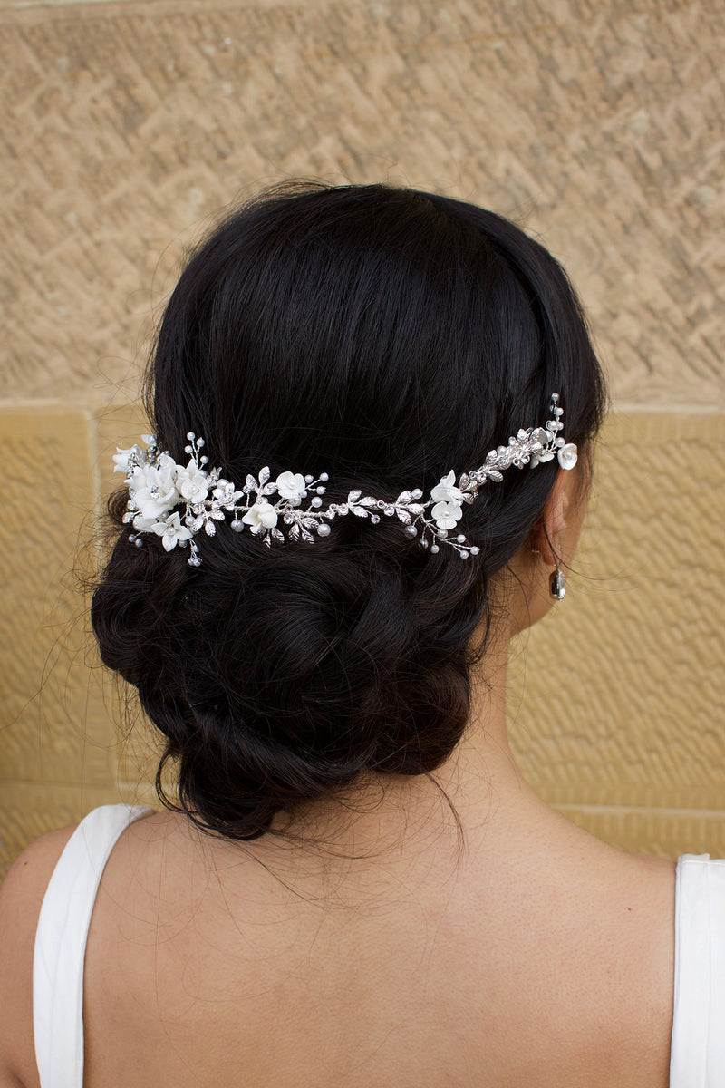 A black haired Bride wears a porcelain flowers silver vine around the back of her head with a stone backdrop