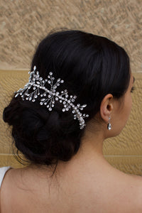 Dark hair model wearing a silver bridal vine around the back of her hair with a sandstone wall backdrop
