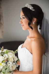 side view of a real bride wearing a silver leaf tiara holding a bouquet of flowers