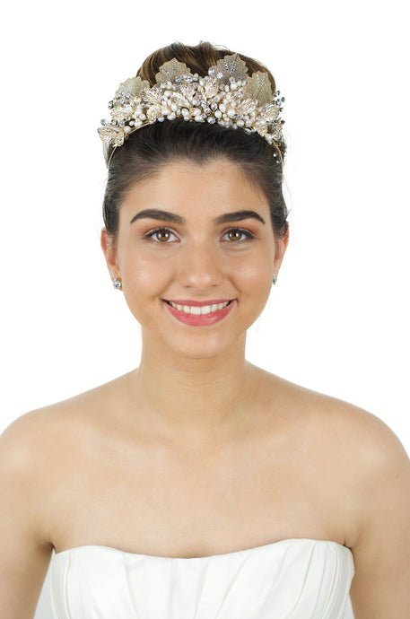 A black haired model wears a  gold tiara with pearls on a White background.