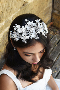 Black Haired model wears a wide headband of flowers with the background of a stone wall