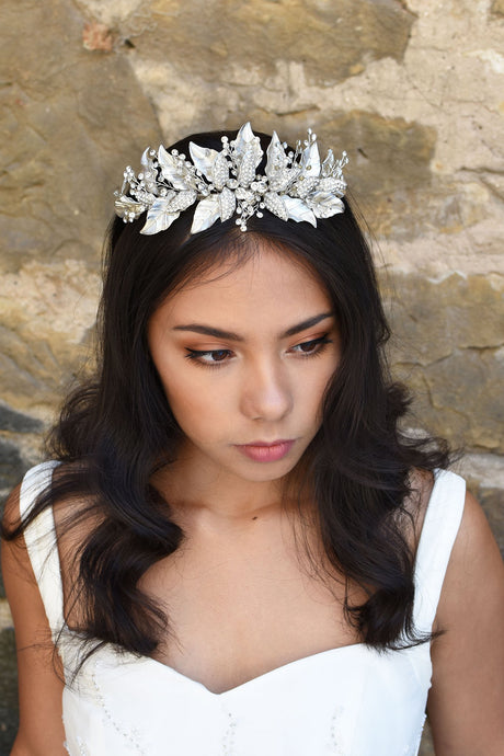 Bridal model wears a silver leaf crown in her dark hair with a stone wall behind her.