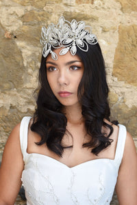 Large Soft Silver Designer Headpiece worn on the forehead of Dark haired Bride in an ivory Bridal Gown with a stone wall backdrop