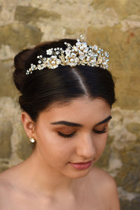 A dark  model wears a gold tiara with pearl flowers against a stone wall background.
