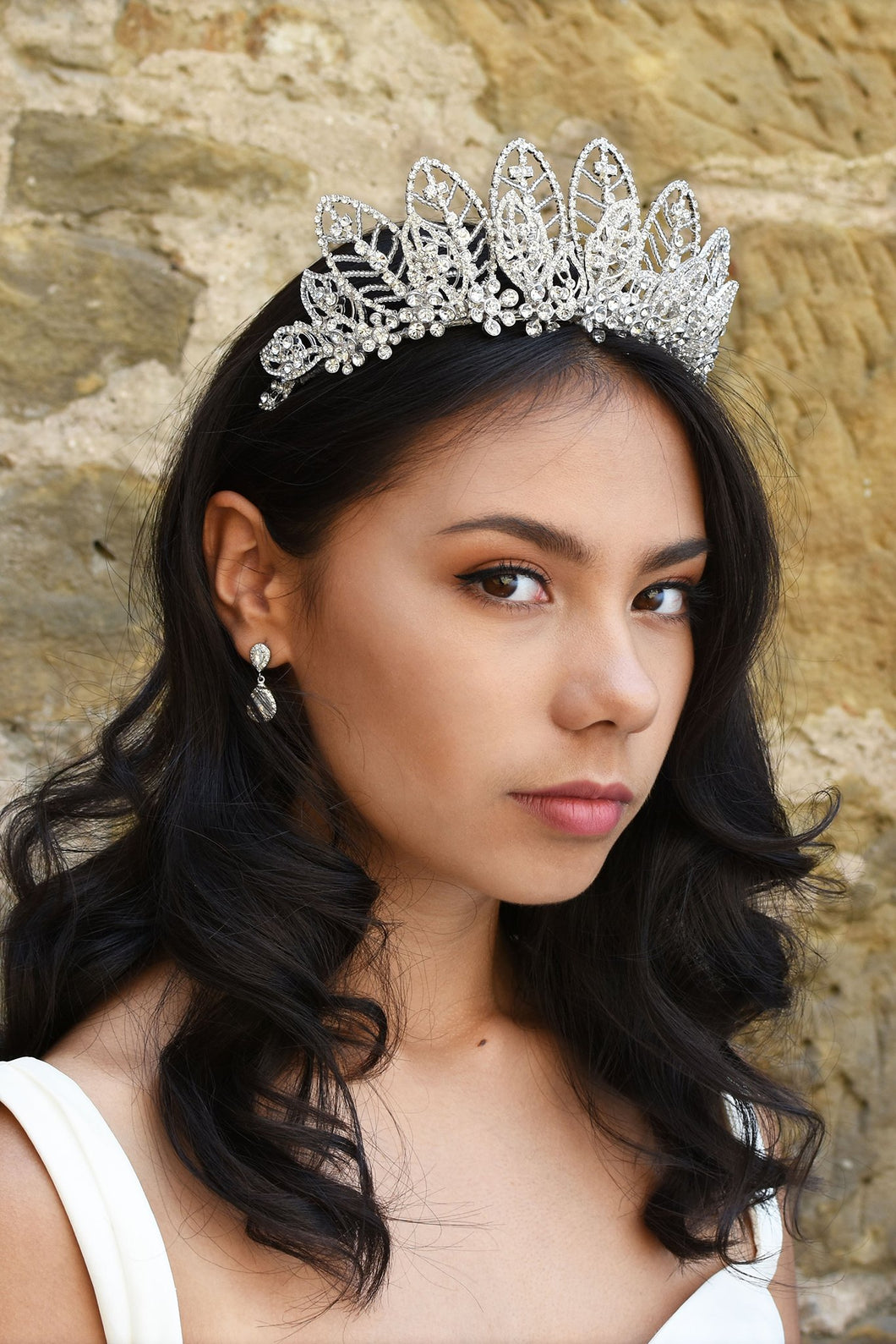 High Tiara with Silver leaves design worn by a dark hair bride in front of an old sandstone wall
