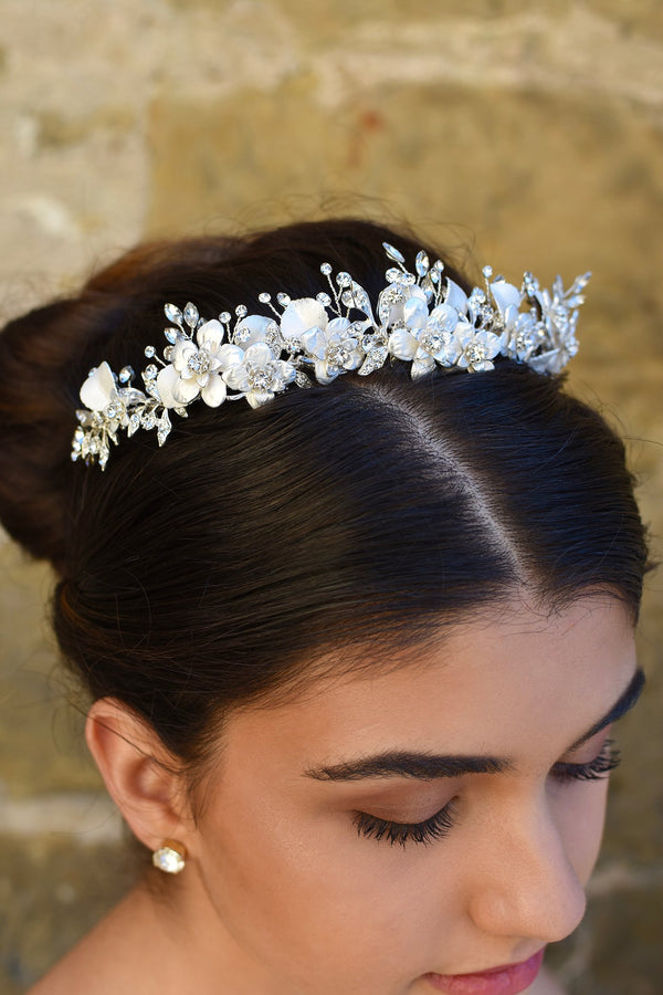 Close up of a white and silver bridal tiara with flowers and leaves worn by a dark hair model with her hair up
