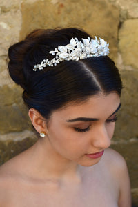 Dark haired bride wears a low silver tiara with a stone wall background