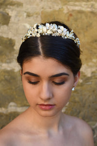 A dark haired model wears a pale gold low tiara with leaves and flowers