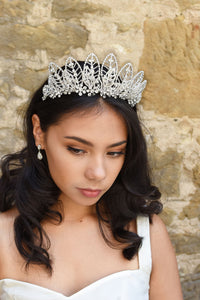 High Bridal Headpiece of silver leaves worn by a dark hair model in front of a  stone wall