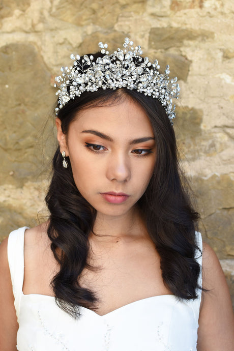 A model Bride wears a high Tiara of real pearls and crystals high on her head. She has dark hair and behind her is a stone wall.