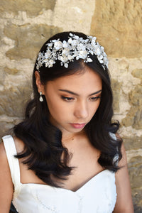 Dark Haired model wears a wide headband of flowers with the background of a stone wall