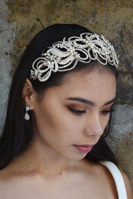 Pale Gold Headband with swirling shapes worn by a dark hair bride with a stone wall backdrop