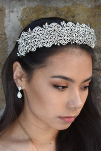 A wide crystal crown is worn by a dark haired model standing in front of a stone wall