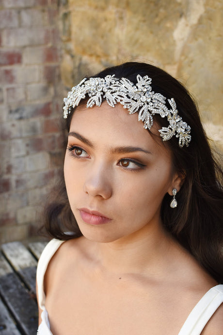 A black hair Bride with brown eyes looks far away while wearing a silver wide Bridal Headband. Behind is a stone wall.
