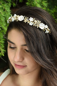 Smiling Dark hair Bridal Model wearing Flower and gold headband with green pine tree background