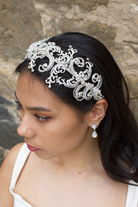 Wide Silver and clear crystal bridal headband worn by a dark haired bride with a stone backdrop