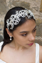 Load image into Gallery viewer, Wide swirling Bridal Headband in Silver with clear crystals worn by a dark haired model with a stone wall backdrop