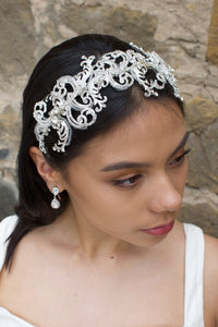 Wide swirling Bridal Headband in Silver with clear crystals worn by a dark haired model with a stone wall backdrop