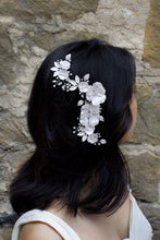 Load image into Gallery viewer, Black haired model wears a white bridal comb in front of a stone wall