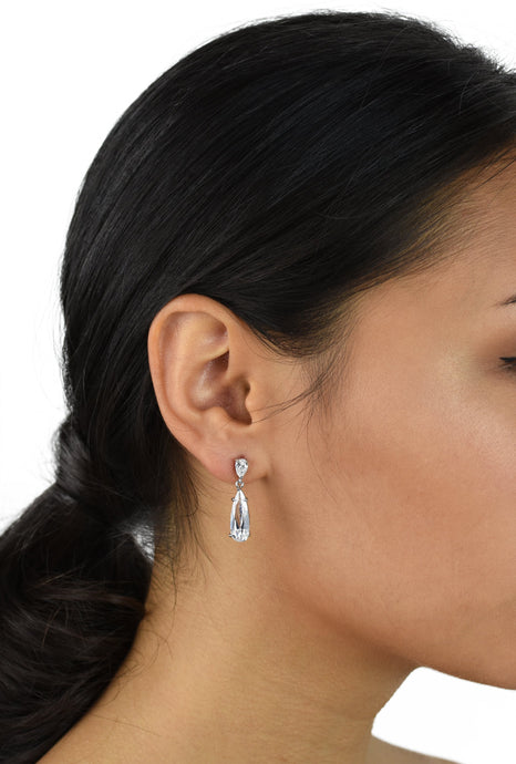 Dark hair model with hair in a pony tail wears a long narrow crystal teardrop earring
