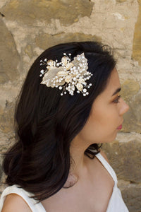 A bride with black hair wears a pale gold bridal hair clip with pearls in her dark hair in front of an old sandstone wall