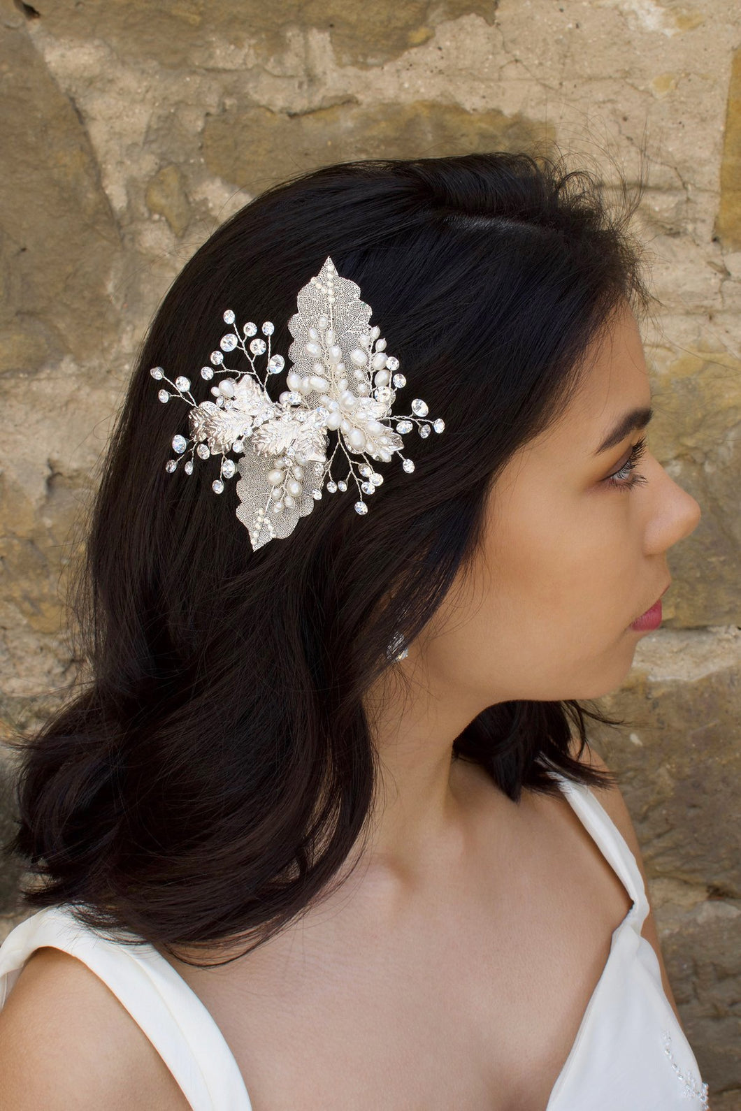 Dark hair bride wears a filigree leaf silver side comb with pearls in front of an old stone wall