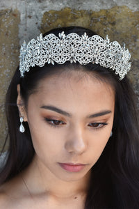 A wide crystal studded tiara is worn at the front of the head of a dark hair model.