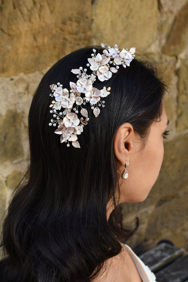 A Dark haired model wears a long Pale gold side comb with flowers and a small earring