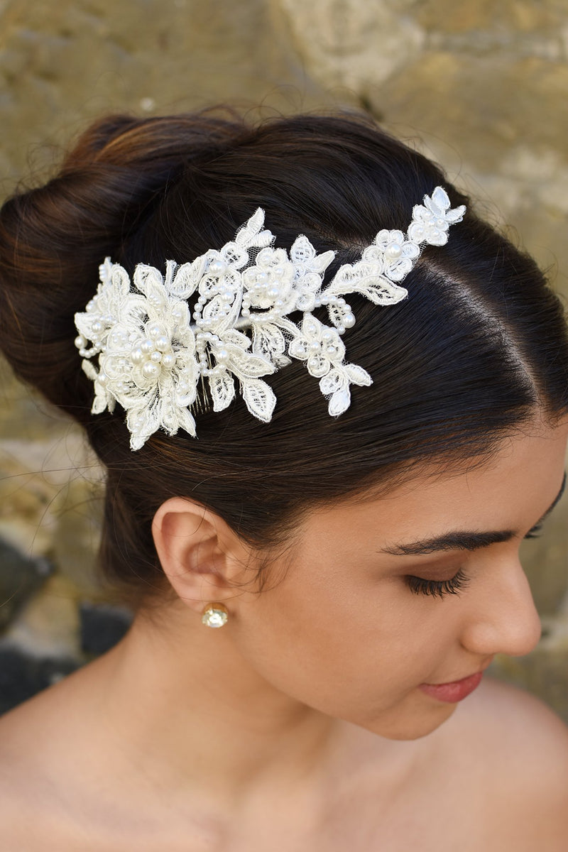 Lace side comb with pearls worn by a dark hair model in front of a stone wall.