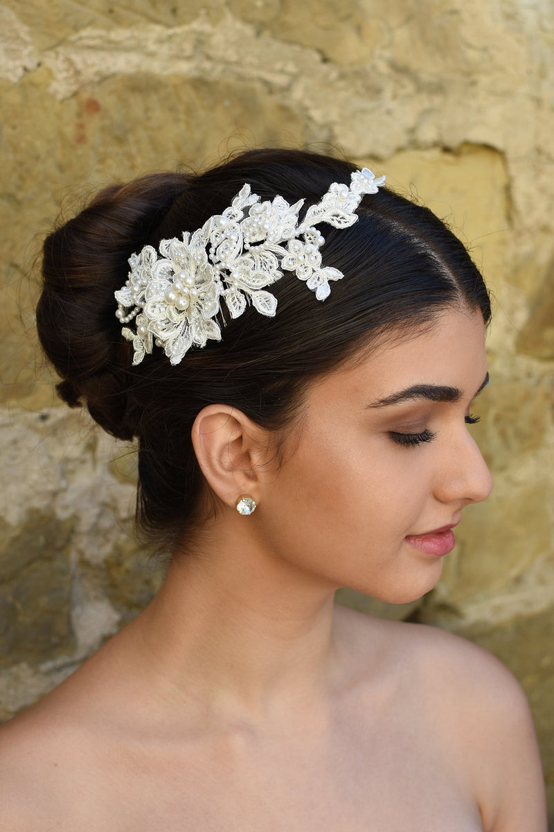 Delicate Lace side comb with pearls worn by a bride in front of a stone wall