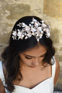 Dark Haired model wears a a pale rose gold wide headband of flowers with the background of a stone wall