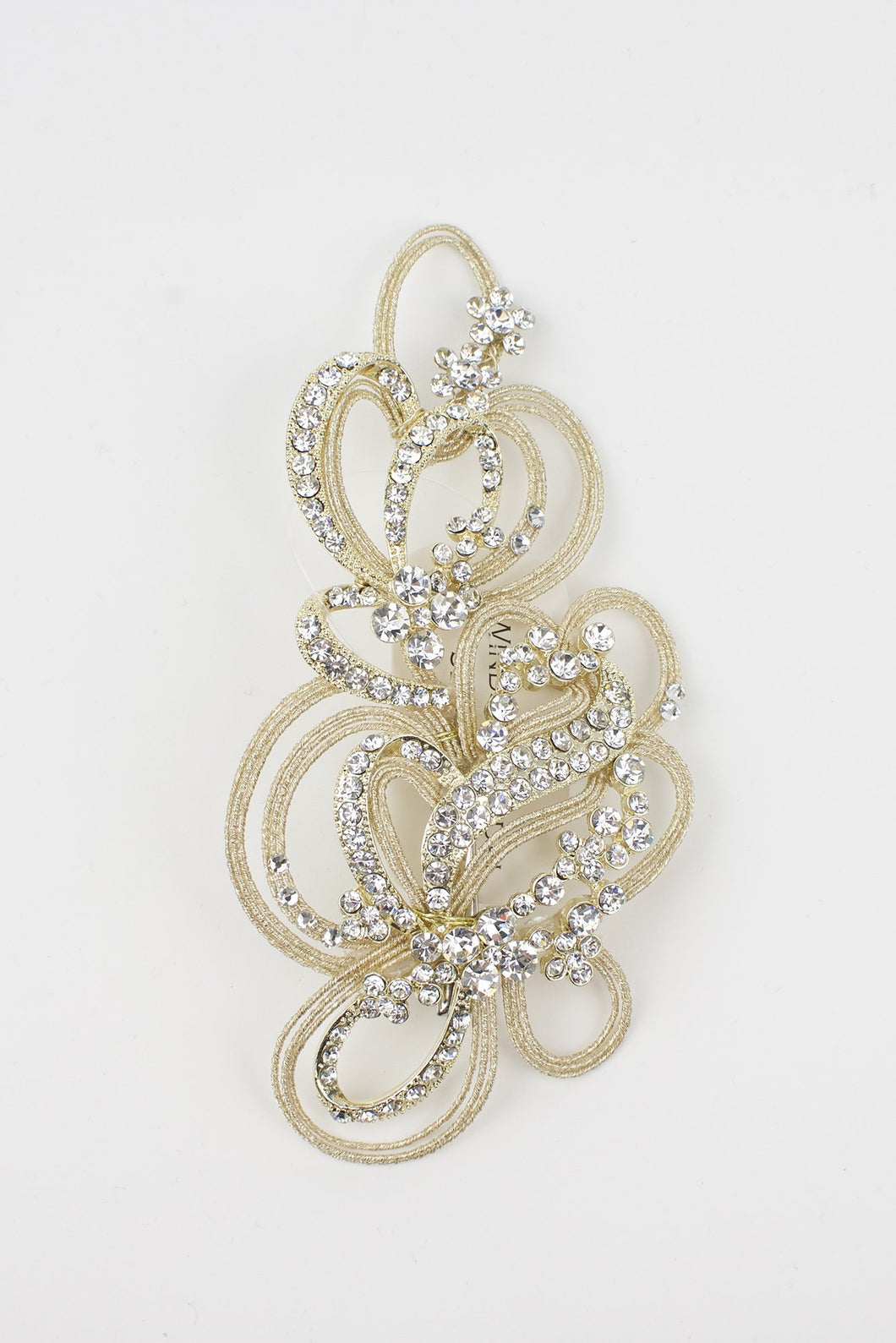 A champagne gold bridal comb with many tiny crystals sits on a pure white background
