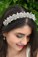 Load image into Gallery viewer, Smiling Bride looks down wearing a gold bridal headband full of tiny crystals with a background of leaves