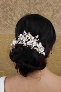 A dark haired bride wears a gold flowers headpiece at the back of her head with a stone wall background