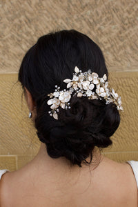 Model Bride wears a Pale Gold Bridal Vine on her dark hair with a wall as background