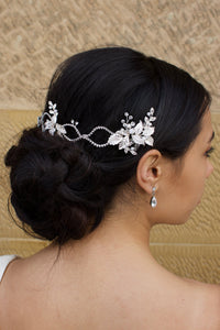 A dark haired model with curly hair wears a silver vine at the back of her head with a stone wall behind