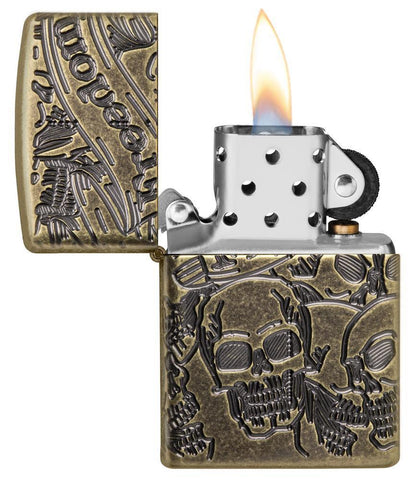 Armor® Antique Brass Skull Design Windproof Lighter with its lid open and lit